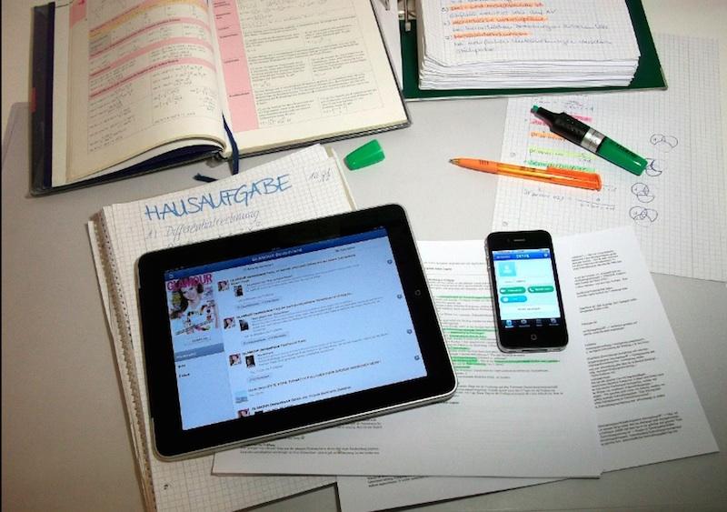 Arbeitsblätter, aufgeschlagene Bücher, Stifte,ein Tablet und ein Smartphone liegen auf einem Tisch