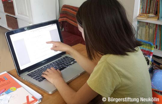 Kind arbeitet am Laptop an Hausaufgaben