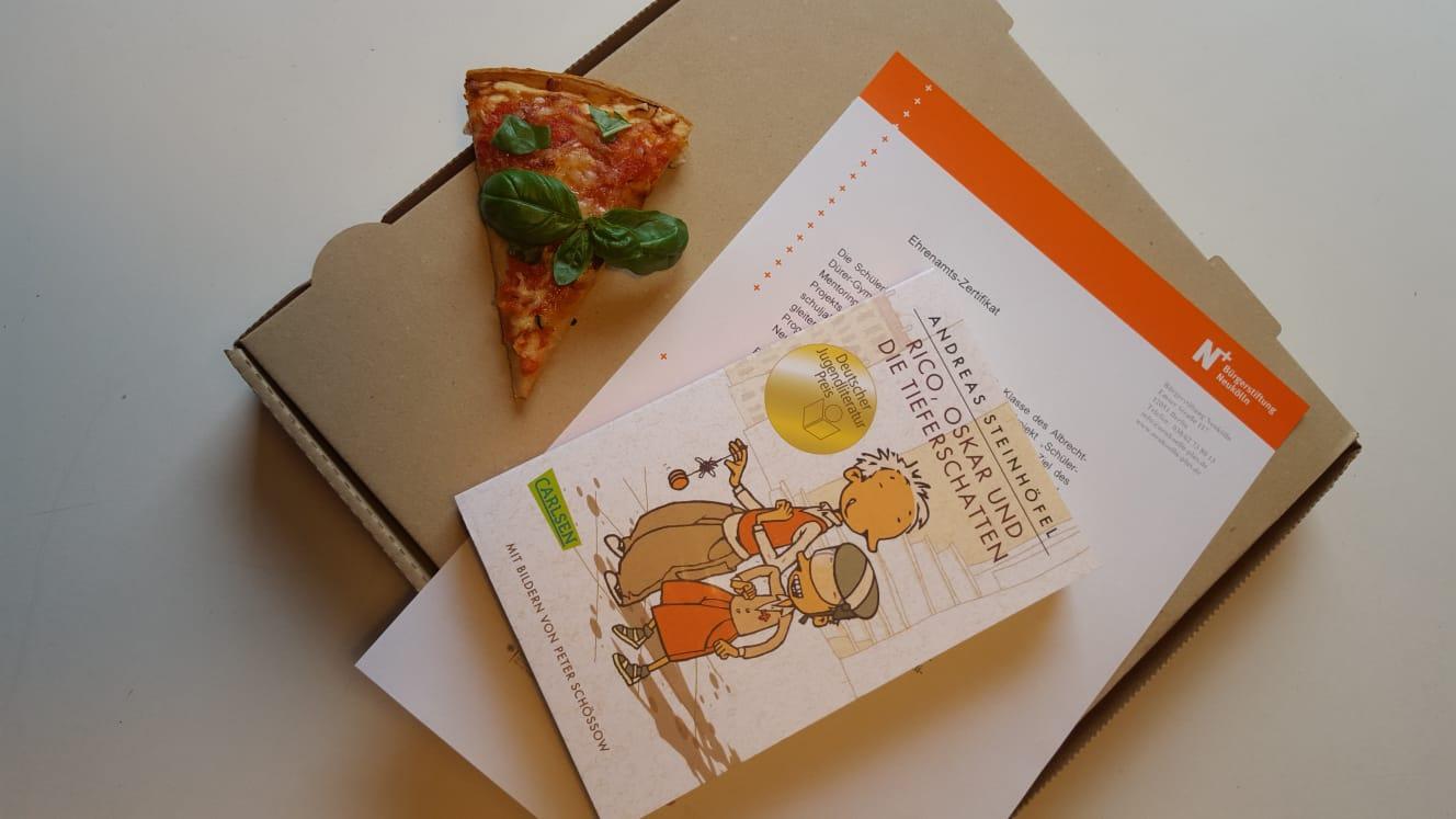 Ein Pizzastück, das Ehrenamts-Zertifikat und ein Buch liegen auf einem Pizzakarton