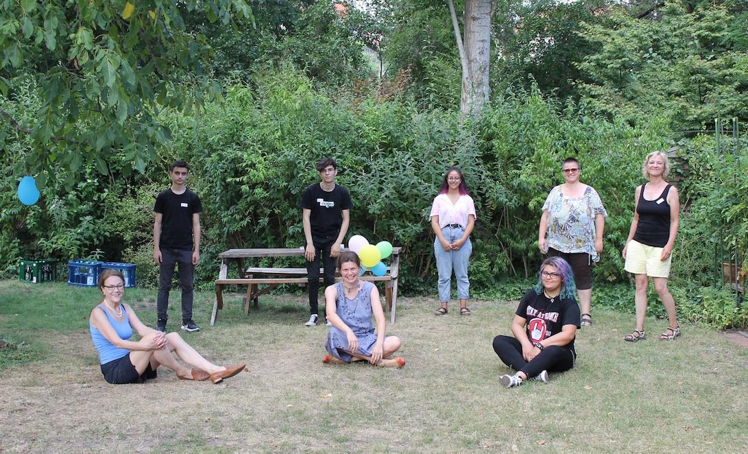 Eine Gruppe von Mentees, Mentor*innen und die Projektleiterin stehen und sitzen im Halbkreis auf dem Rasen beim Smmerfest des Mentorenprojekts und feiern Abschlüsse und Neuanfänge