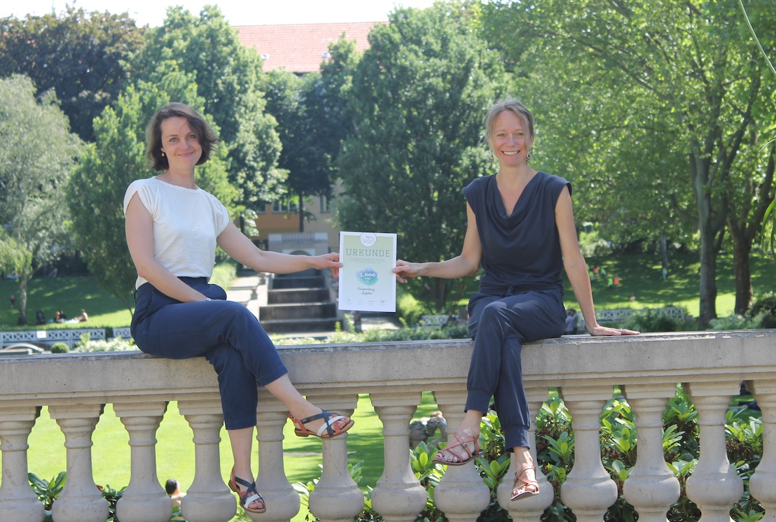 2 Mitarbeiterinnen der Neuköllner Talente sitzen auf steinerner Brüstung im Körnerpark und zeigen die Town & Country Preis-Urkunde
