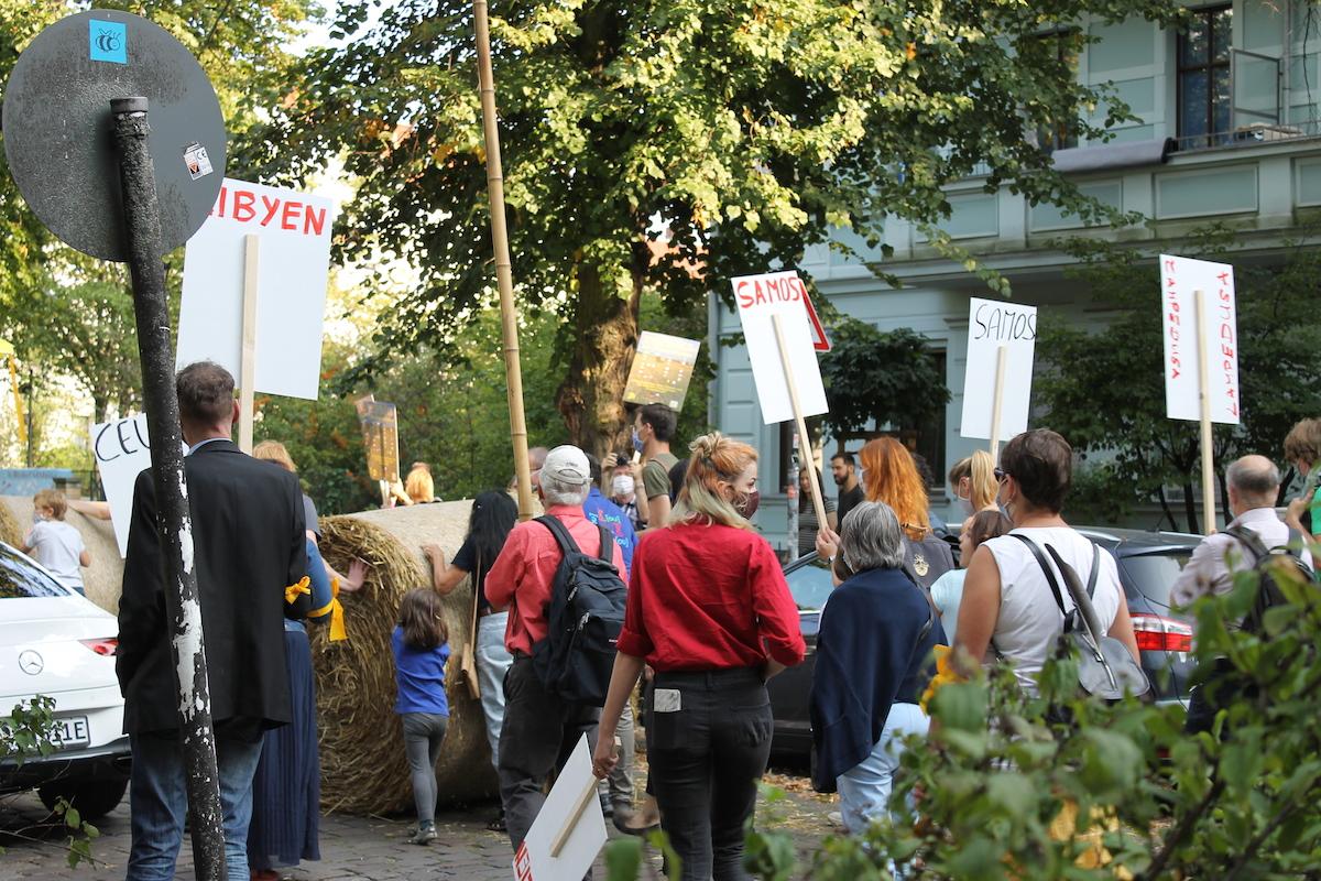 """Menschen von hinten mit Schildern mit den Namen von Flüchtlingslagern auf der Rückseite, Popraci-Demo """"Für ein Europa ohne Grenzen und die Deutsch-Tschechische Freundschaft"""""""