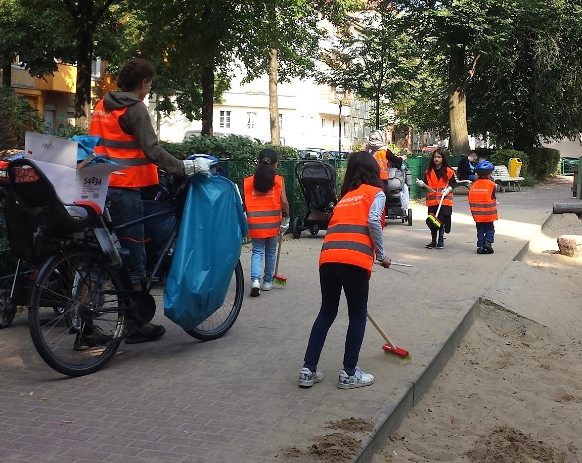 Neuköllner Talente in BSR-Westen räumen mit Besen und Zangen an den Berliner Freiwilligentagen einen Spielplatz auf. Eine Frau mit Fahrrad und blauer Mülltüte begleitet sie.