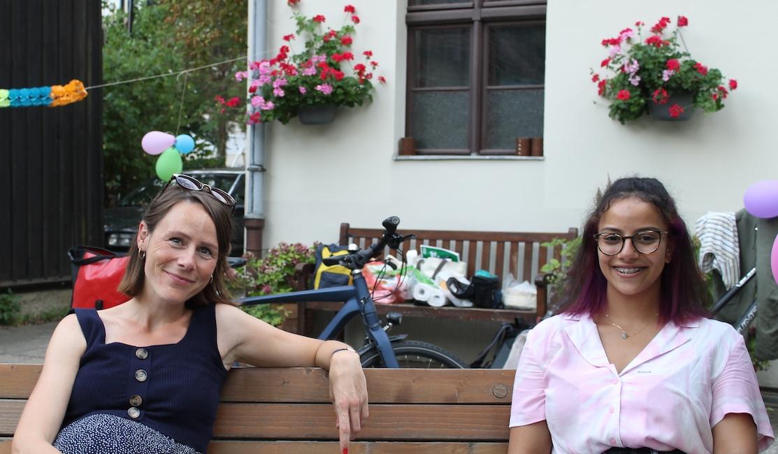 Mentorin und Mentee sitzen mit etwas Abstand lächelnd auf einer Bank