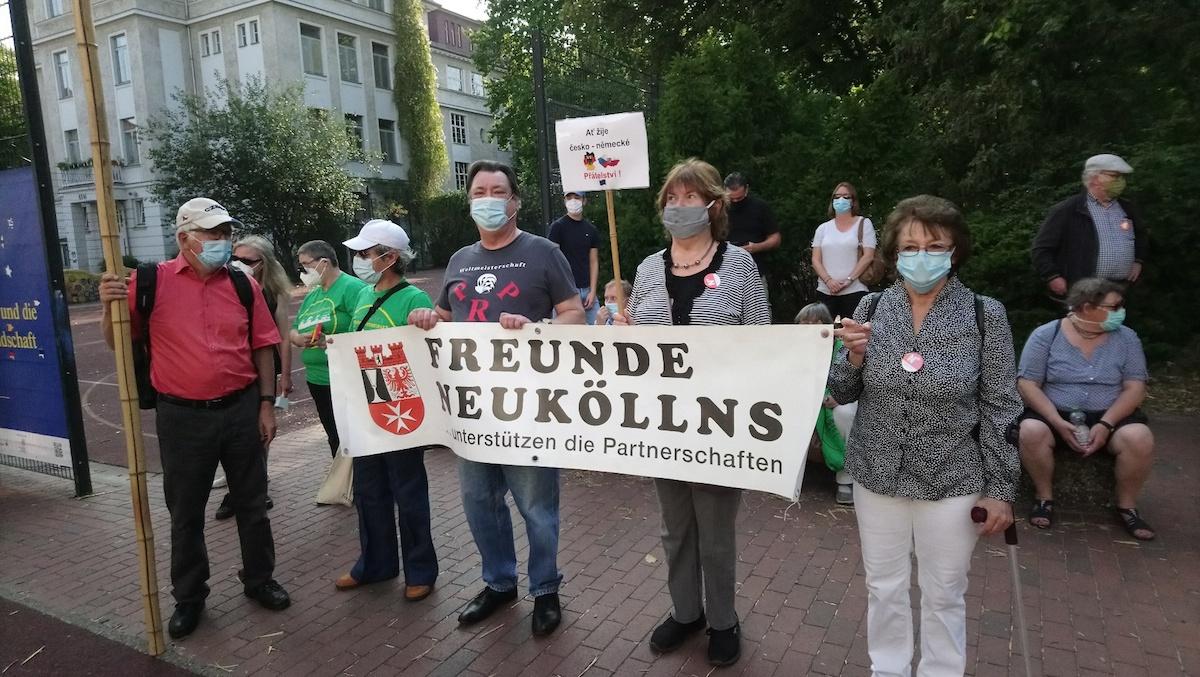 """Drei Troedler*innen im Vordergrund mit Mundschutz halten zusammen ein Banner des Vereins """"Freunde Neuköllns"""" vor sich"""