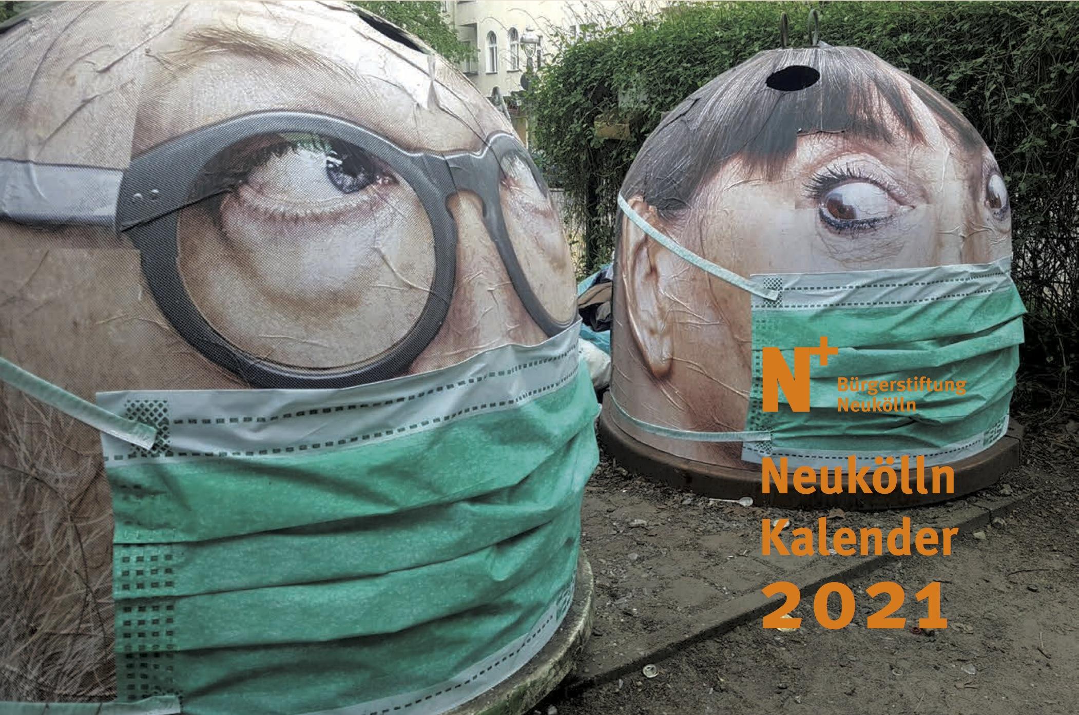 Zwei Mehrweg-Mülltonnen, gestaltet als Gesichter, mit grünen OP-Masken