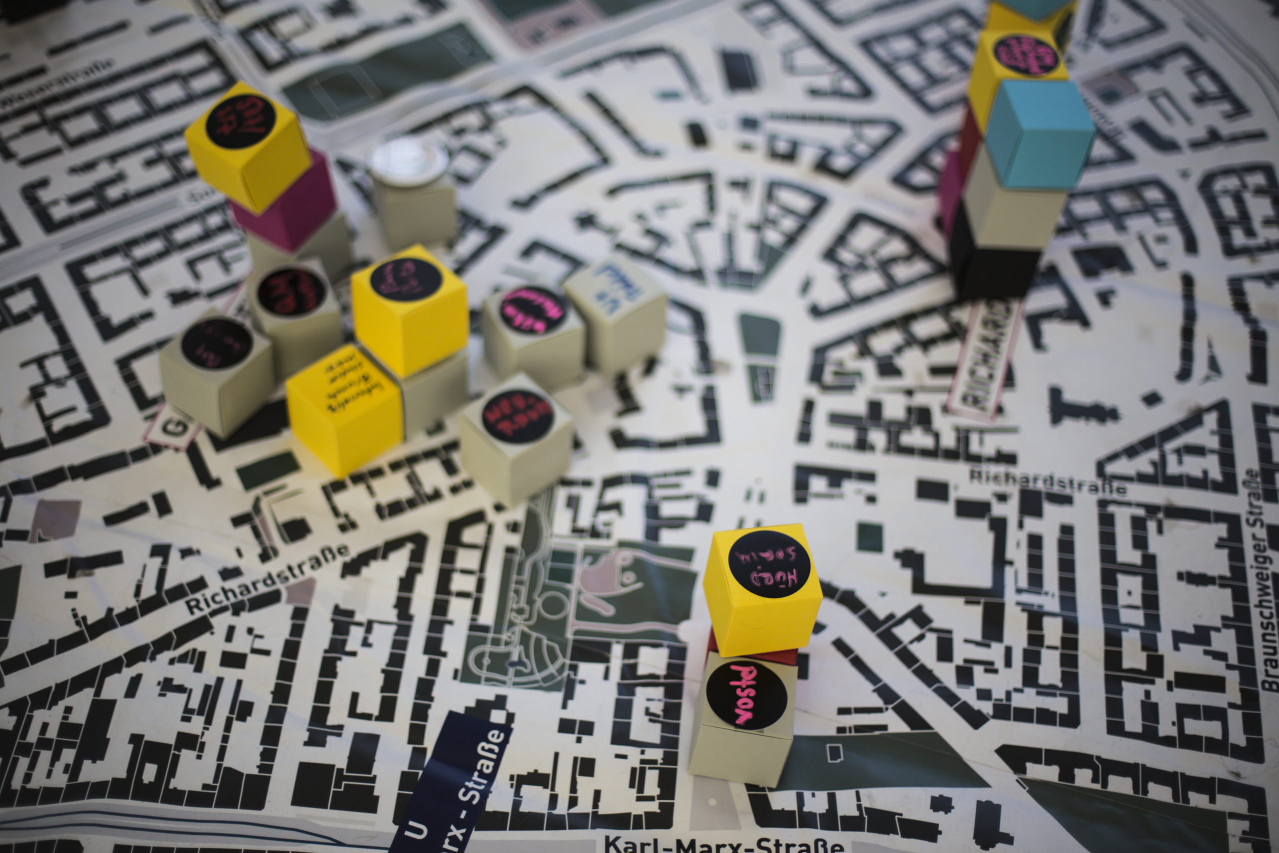 Stadtplan mit bunten beschrifteten Holzbausteinen als Symbol für Bürger*innenbeteiligung in Neukölln