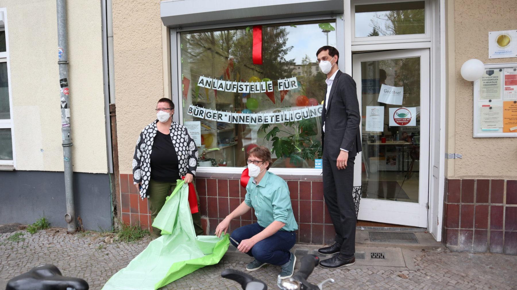 Vor dem Schaufenster des NEZ stehen von links nach rechts Gisela Enders, Juochen Biedermann (hockend) und Martin Hikel