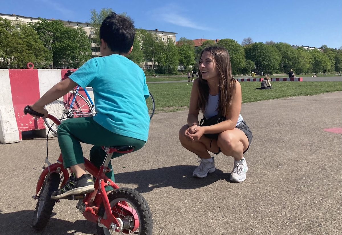 Im Vordergrund Patenkind von hinten auf dem Fahrrad auf dem Tempelhofer, eine junge Frau in der Hocke lächelt das Kind an
