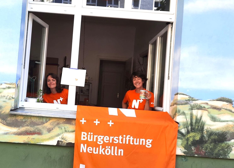 Zwei Frauen schauen aus dem Fenster, eine hält einen Kaffeebecher
