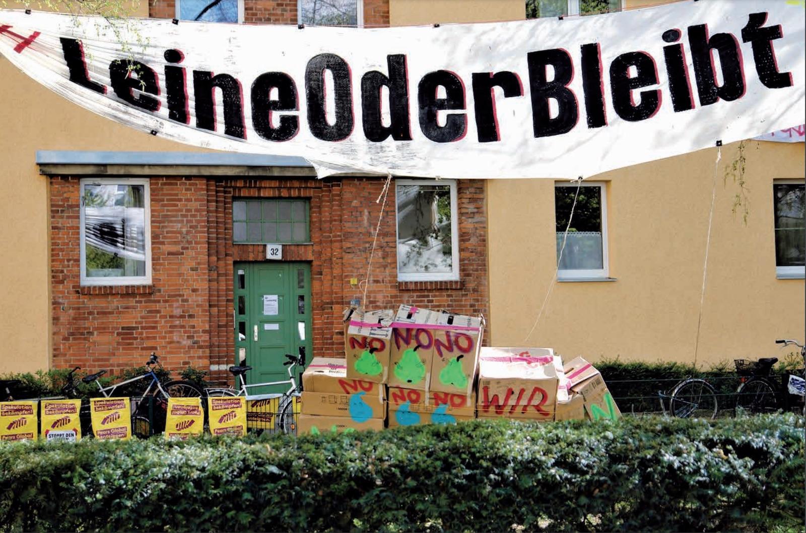 """Banner mit """"LeineOder Bleibt"""" hängt vor einem Haus, vor dem Haus stehen gestapelte Pappkartons mit der Aufschrift """"No"""""""