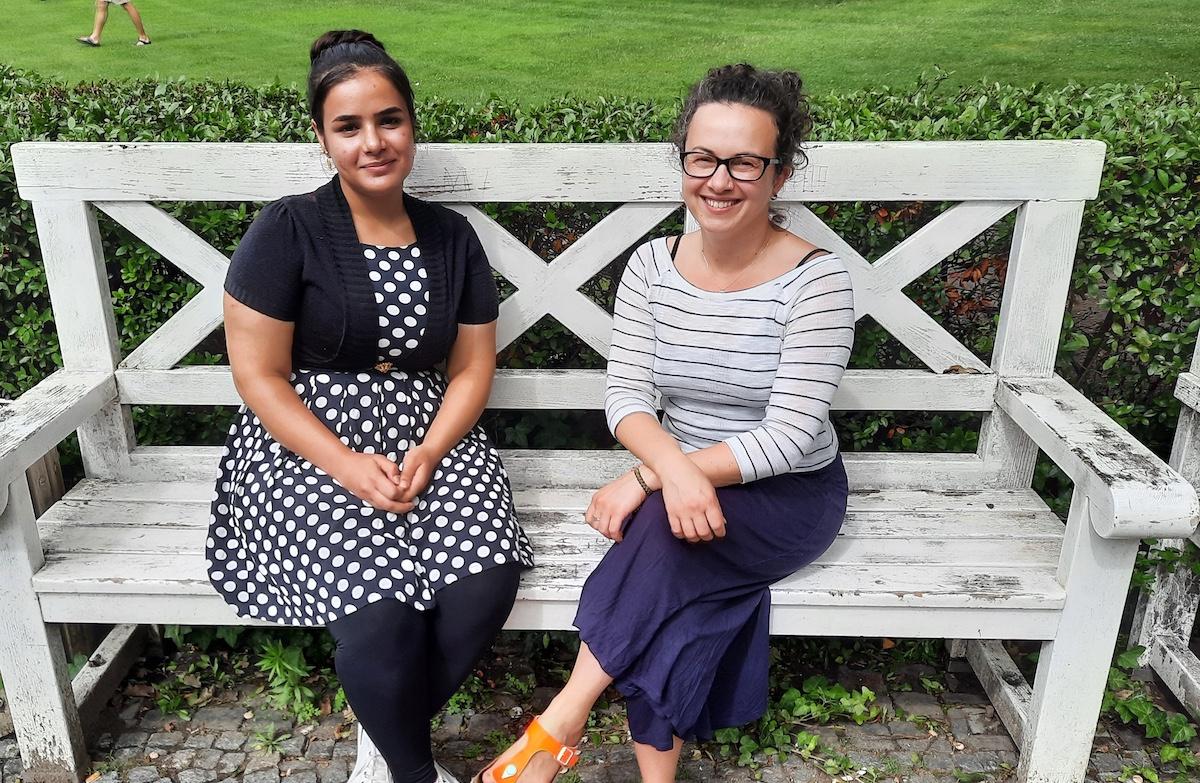 Zwei junge Frauen sitzen lächelnd auf einer Bank vor einer Wiese