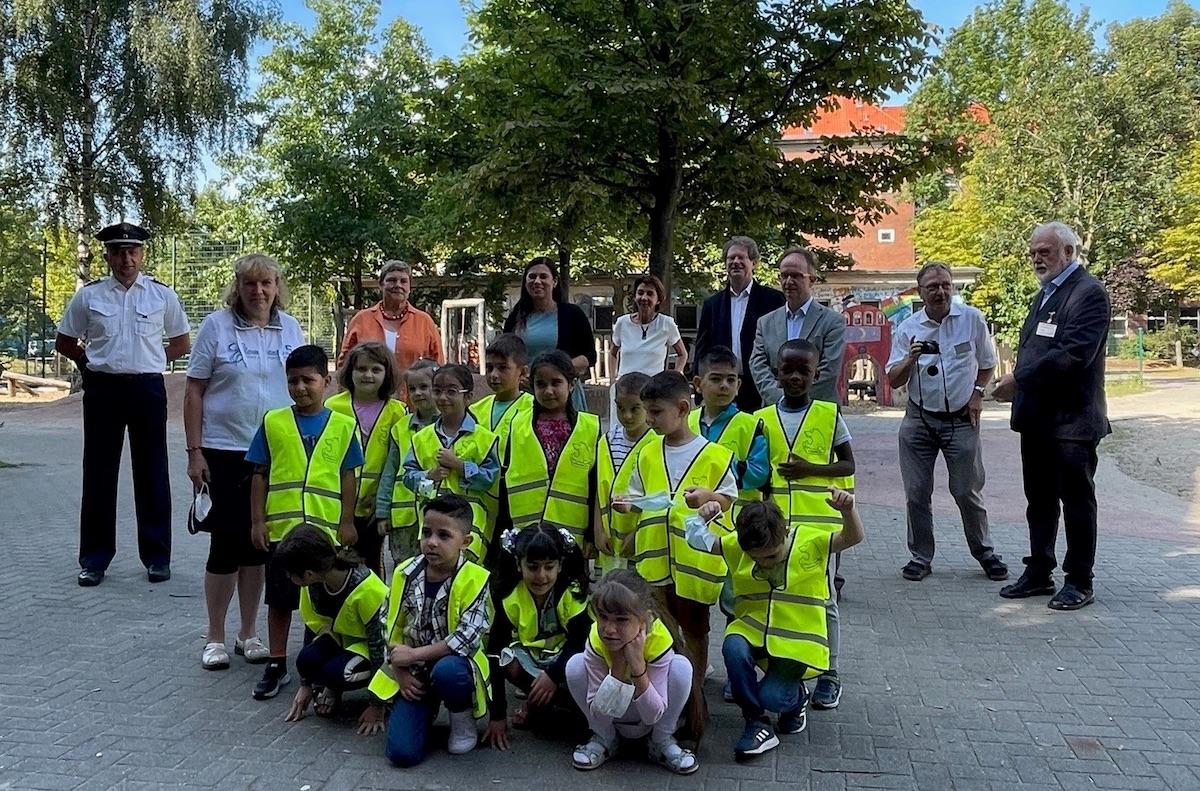 Eine Gruppe Grundschulkinder schaut in die Kamera. 3 hocken vorn, 12 stehen dahinter. Sie tragen gelbe Warnwesten. Hinter den Kindern stehen Frauen und Männer und schauen in das Bild.