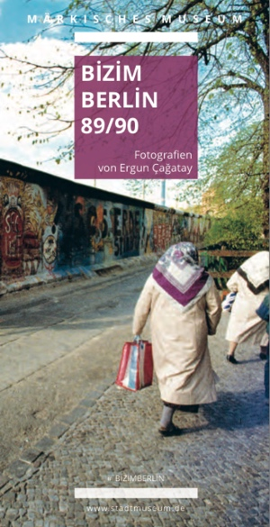 Ausstellungscover, auf dem zwei Frauen mit Kopftuch auf einem Weg neben der Berliner Mauer laufen