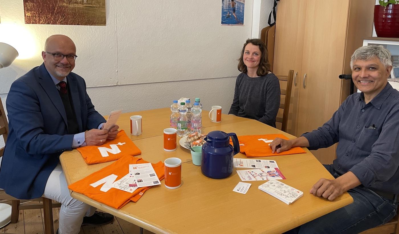 Fritz Felgentreu, Simone Rajilic und Jean-Philippe Laville (v.l.nr.)sitzen mit Abstand am runden Tisch unseres N+Büros. Auf dem Tisch stehen Tassen und eine Kanne, liegen N+T-Shirts, Prospekte