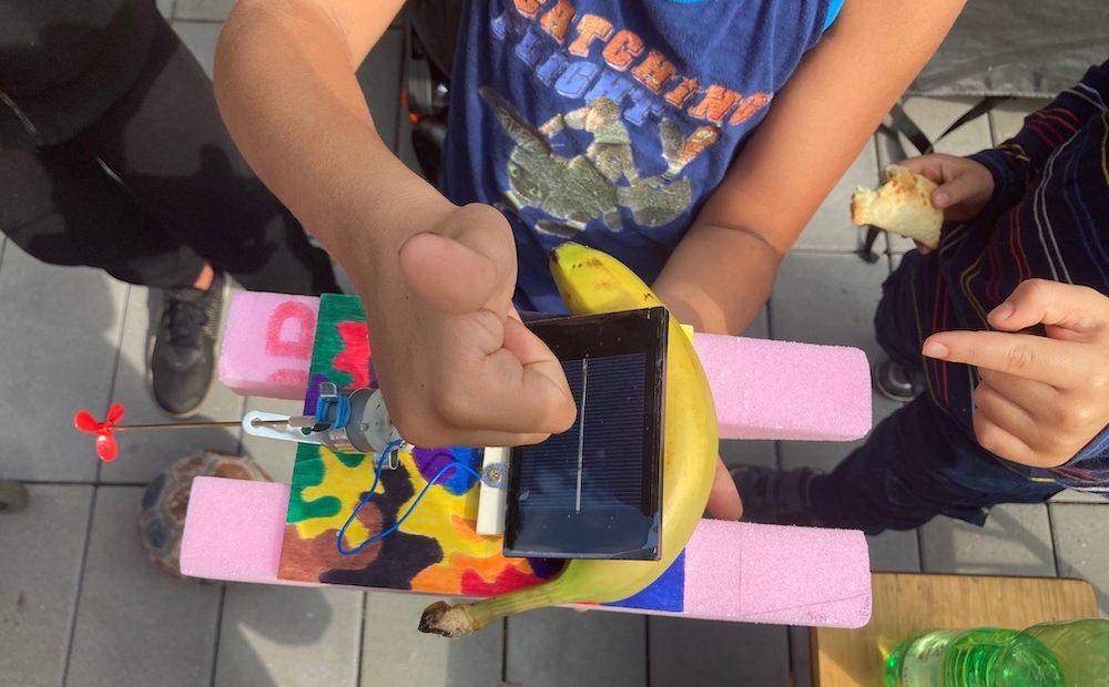 Hochzeigender Daumen eines Kindes über einem selbstgebastelten Solarboot